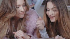 Meninas alegres que encontram-se na cama no quarto brilhante e que usam a tabuleta vídeos de arquivo