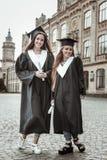Meninas alegres que têm o partido de graduação na universidade imagens de stock