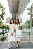Meninas asiáticas bonitas com sacos de compras que andam na rua no th Imagem de Stock