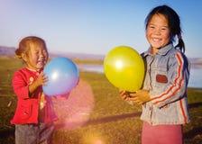 Meninas asiáticas que jogam o conceito rural do Mongolian do balão do lago imagem de stock royalty free