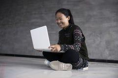Meninas asiáticas que sentam-se no assoalho usando portáteis Imagens de Stock