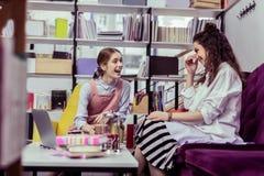 Meninas atrativas de irradiação que vestem equipamentos elegantes e ter a conversação ativa fotografia de stock royalty free