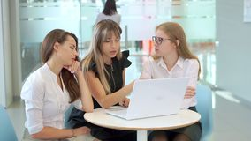 Meninas atrativas novas em uma reunião de negócios ativamente para discutir e olhar o portátil video estoque