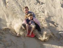 Meninas aventurosas que embarcam abaixo das dunas de areia Imagem de Stock Royalty Free