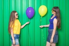 Meninas bonitas com os balões coloridos no fundo verde da parede Conceito da forma imagens de stock royalty free