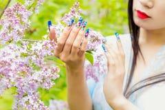 Meninas bonitas das mãos com os pregos longos falsificados com as imagens que guardam um ramo do lilás no jardim, em seu batom do Imagem de Stock