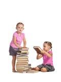 Meninas bonitas dos gêmeos com a pilha dos livros isolados foto de stock royalty free