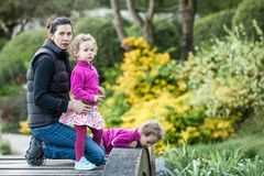 Meninas bonitas em revestimentos cor-de-rosa e em saias coloridas com a mãe na ponte Fotografia de Stock Royalty Free