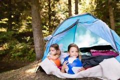 Meninas bonitas na barraca que acampam na floresta Foto de Stock