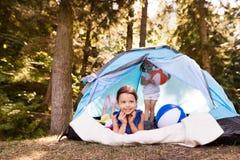 Meninas bonitas na barraca que acampam pelo lago Foto de Stock Royalty Free