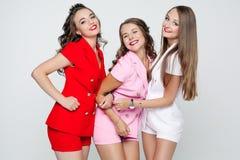 Meninas bonitas nos ternos coloridos que colam para fora e que mostram a paz Fotografia de Stock Royalty Free