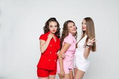 Meninas bonitas nos ternos coloridos que colam para fora e que mostram a paz Fotos de Stock Royalty Free