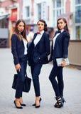 Meninas bonitas nos ternos pretos que levantam na rua Imagens de Stock Royalty Free