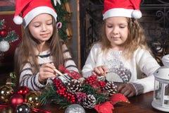 Meninas bonitas que decoram brinquedos do Natal fotografia de stock royalty free