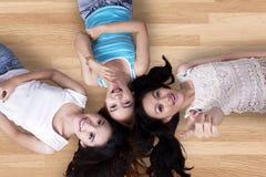Meninas bonitas que encontram-se para baixo no assoalho de madeira Imagens de Stock