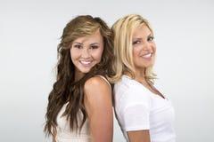 2 meninas bonitas que sorriem contra um fundo branco Fotos de Stock Royalty Free