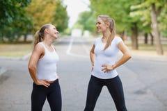 Meninas bonitas, 'sexy' dos esportes que exercitam em um fundo do parque Conceito do estilo de vida da aptidão Copie o espaço Fotografia de Stock