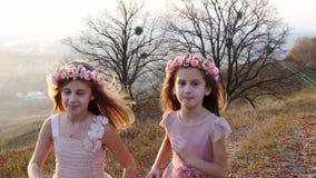 Meninas bonitos felizes que correm a ascendente no monte Paisagem surpreendente no fundo filme