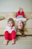 Meninas bonitos no sofá de cabeça para baixo Imagens de Stock