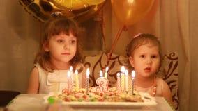 Meninas bonitos pequenas e no bolo de aniversário no partido As crianças felizes engraçadas discutem e expressam o descontentamen video estoque