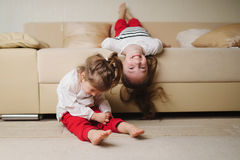 Meninas bonitos pequenas no sofá de cabeça para baixo Fotos de Stock Royalty Free