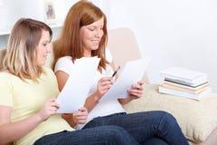 Meninas bonitos que sentam-se com notas de papel Fotos de Stock