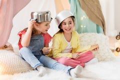 Meninas com o kitchenware que joga na barraca em casa imagens de stock royalty free
