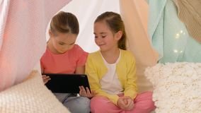 Meninas com o PC da tabuleta na barraca das crianças em casa vídeos de arquivo