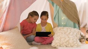 Meninas com o PC da tabuleta na barraca das crianças em casa filme