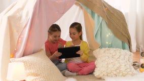Meninas com o PC da tabuleta na barraca das crianças em casa