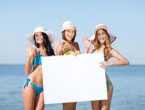 Meninas com placa vazia na praia Imagem de Stock Royalty Free