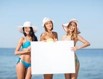 Meninas com placa vazia na praia foto de stock