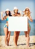 Meninas com placa vazia na praia fotografia de stock