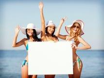 Meninas com placa vazia na praia Imagens de Stock