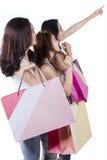 Meninas com sacos de compras que apontam no copyspace Fotografia de Stock