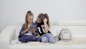 Meninas com uma tabuleta Retrato de dois amigos fêmeas dentro Dois adolescentes que olham o PC da tabuleta do portátil filme