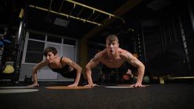 Meninas contra meninos Pushup da força do impulso-acima do homem e da mulher do Gym video estoque