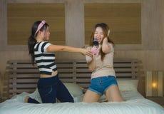 Meninas coreanas asiáticas felizes e entusiasmados novas que cantam junto a música em linha do karaoke com o microfone e o telefo foto de stock