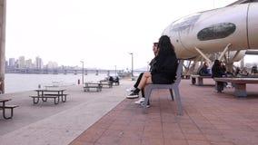 Meninas coreanas do estudante que sentam-se junto no banco no parque e que tomam, Seoul, Coreia do Sul video estoque