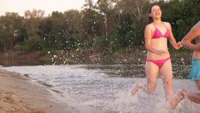 Meninas corridas na areia ao longo da costa na praia que espirra gotas e riso da água Adolescentes felizes e livres na