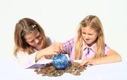 Meninas - crianças que enchem o porco da economia com o dinheiro imagem de stock royalty free