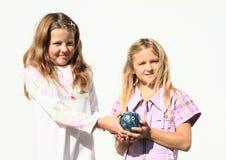 Meninas - crianças que mantêm o porco da economia completo do dinheiro fotografia de stock