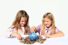 Meninas - crianças que enchem o porco da economia com o dinheiro Fotografia de Stock