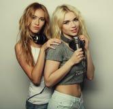 Meninas da beleza com um microfone que cantam e que dançam Imagens de Stock