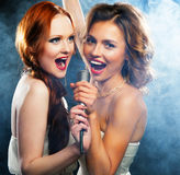 Meninas da beleza com um microfone que cantam e que dançam Foto de Stock Royalty Free