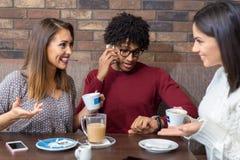 Meninas da bisbolhetice que falam no café quando o homem estiver no telefone Imagem de Stock