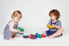 Meninas da criança que jogam com blocos de apartamentos Fotografia de Stock