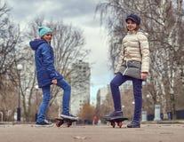 Meninas da escola com os waveboards no parque Imagem de Stock