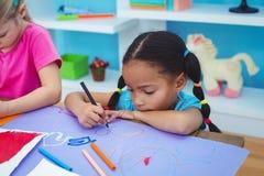 Meninas da escola que pintam uma imagem fotografia de stock