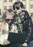 Meninas da escola que usam o portátil no banco Imagens de Stock